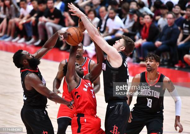 TOPSHOT Toronto Raptors OG Anunoby is blocked by Houston Rockets James Harden and Isaiah Hartenstein in their NBA preseason basketball game in...