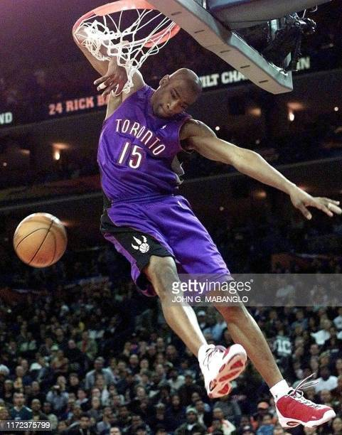 Toronto Raptors player Vince Carter gets his arm tangled in the net during the NBA All-Star Slam Dunk contest 12 February, 2000 at the Arena in...