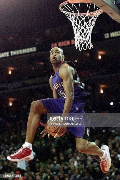 Toronto Raptors player Vince Carter passes the ball between his legs during one of his slam dunk attempts in the NBA All-Star Slam Dunk contest 12...