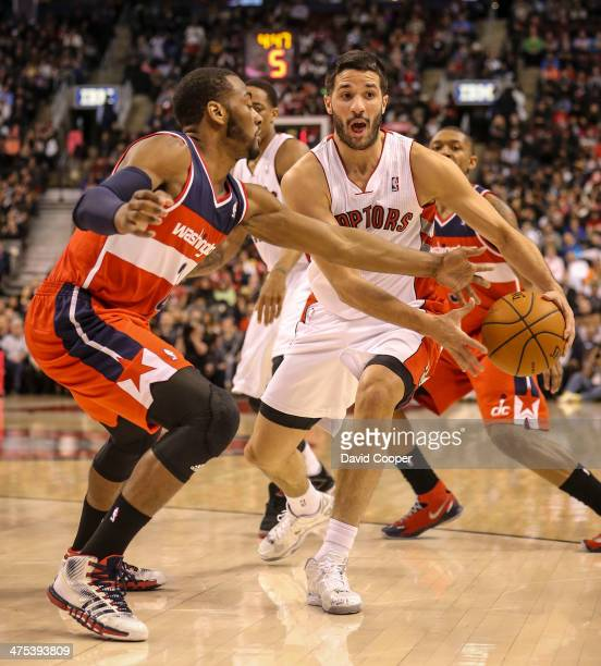 Toronto Raptors point guard Greivis Vasquez looks to pass as he is guarded by Washington Wizards point guard John Wall during the game between the...