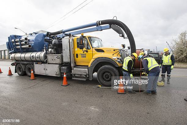 TORONTO ON NOVEMBER 29 Toronto Water workers look into a man hole as a high pressure hose is lowered into a clogged sewer pipe The high pressure...