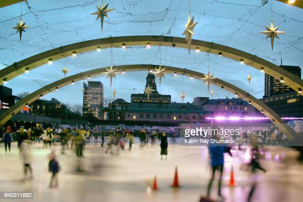 toronto winter fun. ice skating on nathan phillips square - focus on background stock pictures, royalty-free photos & images