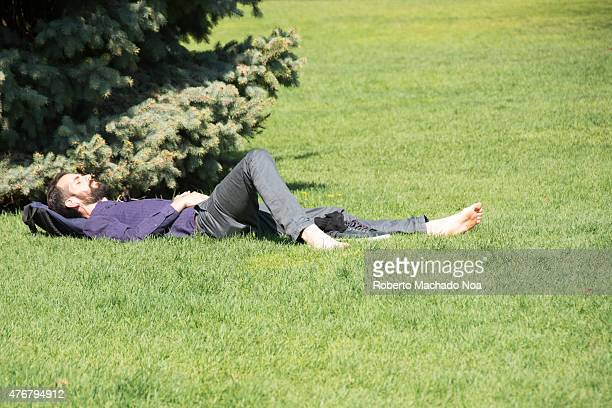 Torontonian enjoying the Spring sun in Queen's Park Resting barefoot man lying on green grass under spruce