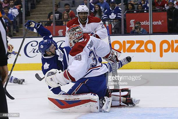 TORONTO ON SEPTEMBER 26 Toronto's Byron Froese falls in between Montreal's Devante SmithPelly and goalie Mike Condon during the preseason game...