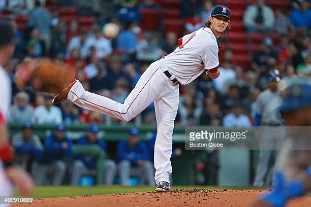 Toronto's Jose Reyes dives back safely into first base as Red Sox pitcher Clay Buchholz fires a first inning pick off attempt to first baseman Mike...