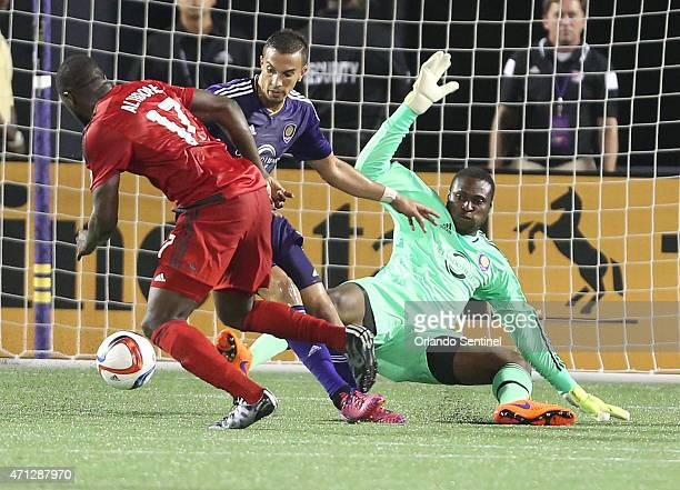 Toronto's Jozy Altidore scores a goal past fallen Orlando goalkeeper Donovan Ricketts and Orlando's Seb Hines on Sunday, April 26 at the Orlando...