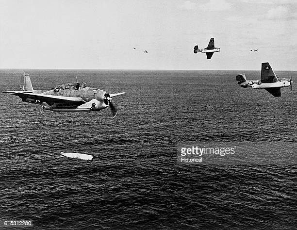 Torpedo planes from the Naval Air Station at Norfolk Virginia fly maneuvers over the water The plane on the left has just fired its torpedo