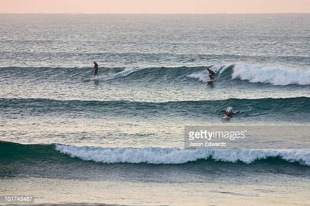 Surfers crowd the lineup as waves peel into the shore before dawn.