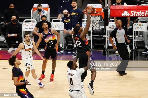Torrey Craig of the Phoenix Suns slam dunks the ball over JaMychal Green of the Denver Nuggets after a pass from Cameron Payne during the second half...