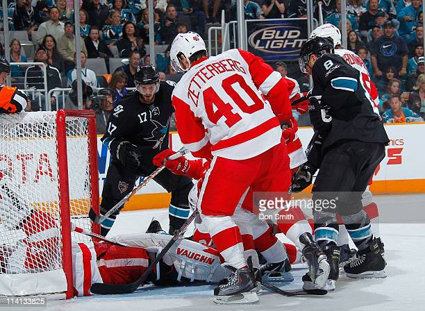 Torrey Mitchell and Joe Pavelski of the San Jose Sharks look for a rebound against Henrik Zetterberg of the Detroit Red Wings in Game Seven of the...