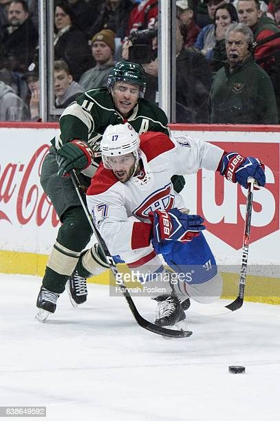 Torrey Mitchell of the Montreal Canadiens controls the puck against Zach Parise of the Minnesota Wild during the second period of the game on January...