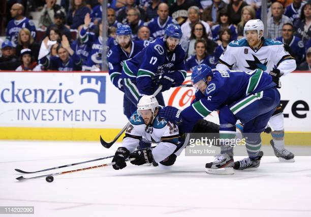 Torrey Mitchell of the San Jose Sharks dives to poke at the puck as Ryan Kesler and Christian Ehrhoff of the Vancouver Canucks defend the play in...