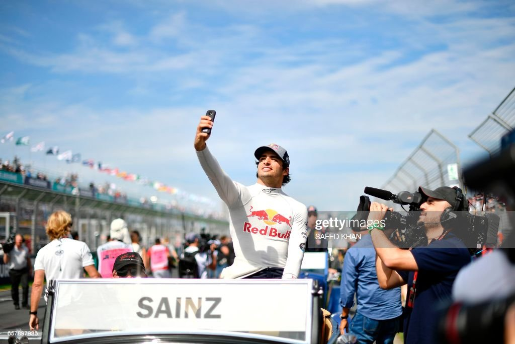 TOPSHOT - Torro Rosso's Spanish driver Carlos Sainz Jr takes part in the drivers parade prior to the start of the Formula One Australian Grand Prix in Melbourne on March 26, 2017. /