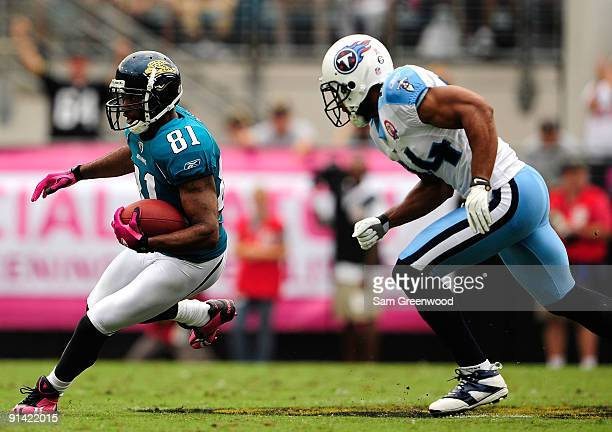 Torry Holt of the Jacksonville Jaguars is chased by Chris Hope of the Tennessee Titans during the game at Jacksonville Municipal Stadium on October 4...