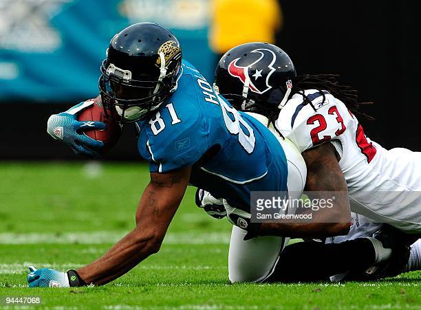 Torry Holt of the Jacksonville Jaguars is tackled by Dunta Robinson of the Houston Texans during the game at Jacksonville Municipal Stadium on...