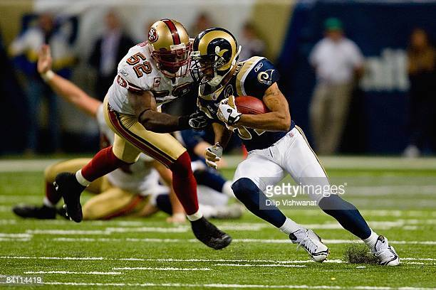 Torry Holt of the St Louis Rams carries the ball against Patrick Willis of the San Francisco 49ers at the Edward Jones Dome on December 21 2008 in St...