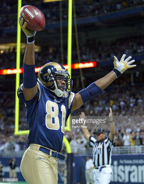 Torry Holt of the St. Louis Rams raises his arms in celebration of his touchdown against the New Orleans Saints during the 1st half of the game at...