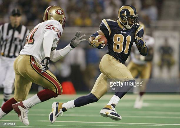 Torry Holt of the St Louis Rams runs the ball across midfield against the San Francisco 49ers on September 14 2003 at the Edward Jones Dome in St...