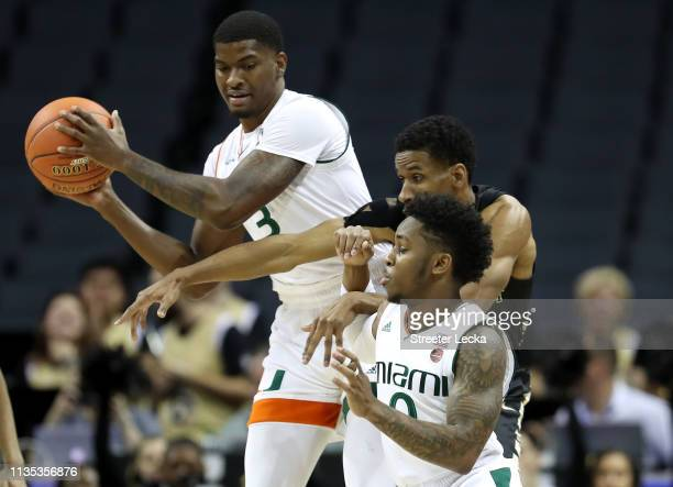 Torry Johnson of the Wake Forest Demon Deacons tries to break up a play between teammates Anthony Lawrence II and Chris Lykes of the Miami Hurricanes...
