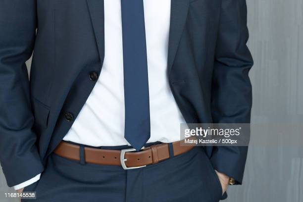 torso of a businessman standing with hands clenched in middle position in a classic navy blue suit - ベルト ストックフォトと画像