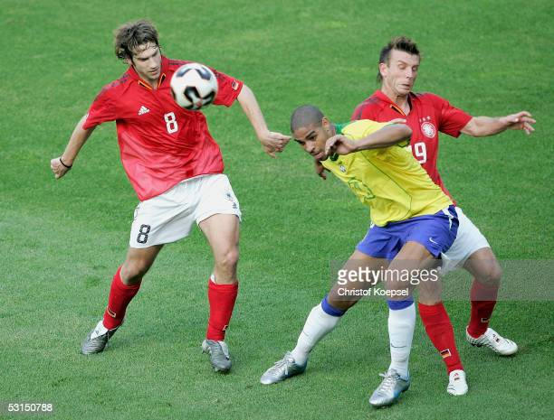 Torsten Frings and Bernd Schneider of Germany tackle Adriano of Brazil during the Semi Final Match between Germany and Brazil for the FIFA...