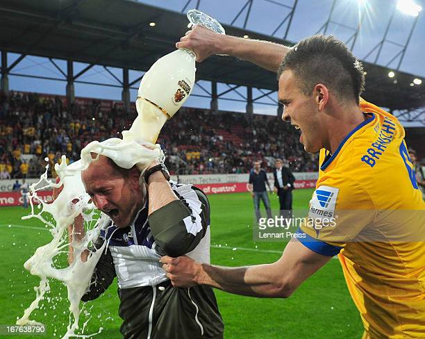 Torsten Lieberknecht head coach of Braunschweig has beer poured over him by Orhan Ademi as they celebrate promotion to the 1 Bundesliga after the 2...