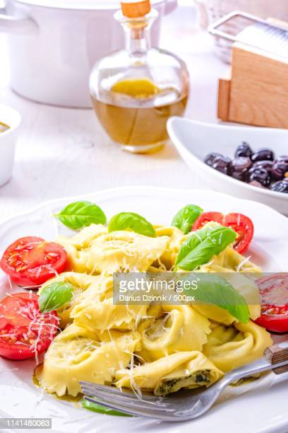 tortellini dish with gratedparmesanand tomato haves and basil leaves on white plate after preparation - after stock photos and pictures