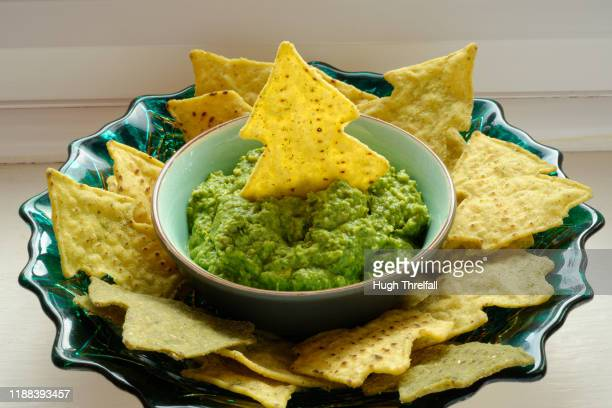 tortilla chips in the shape of a christmas tree and with a green pea dip. - hugh threlfall stock pictures, royalty-free photos & images