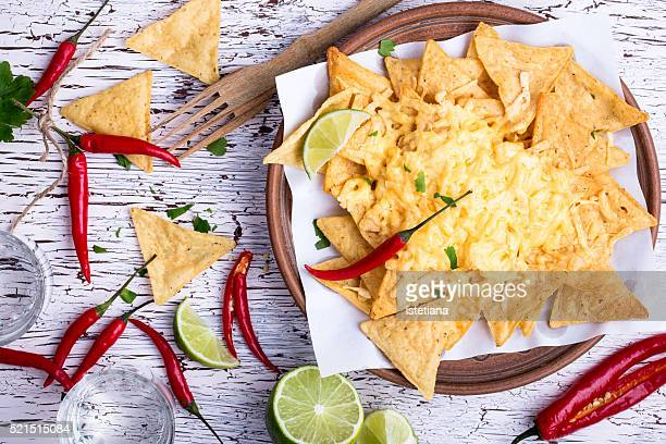 Tortilla chips  with cheese, chili pepper, lime on a wooden table viewed from above. Nachos, tex-mex dish. Mexican food