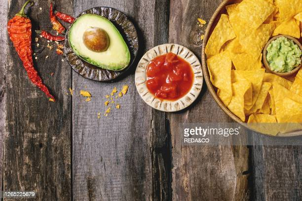 Tortilla nachos corn chips with avocado guacamole and tomato sauce served in wood plate with half of avocado and chilli peppers over old wooden...