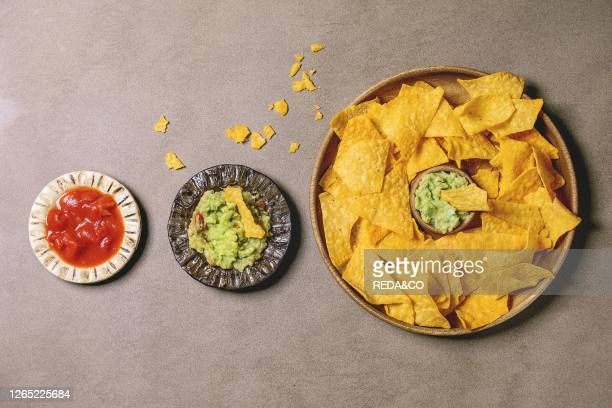 Tortilla nachos corn chips with avocado guacamole and tomato sauce served in wood plate over brown texture background Flat lay space