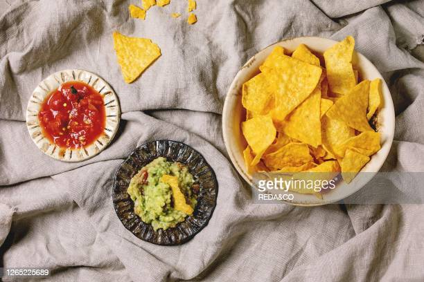 Tortilla nachos corn chips with avocado guacamole and tomato sauce served in ceramic bowl over linen folded cloth as background Flat lay space