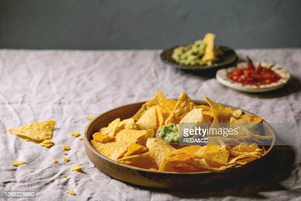 Tortilla nachos corn chips with avocado guacamole and tomato sauce served in wood plate on linen table cloth Mexican snack