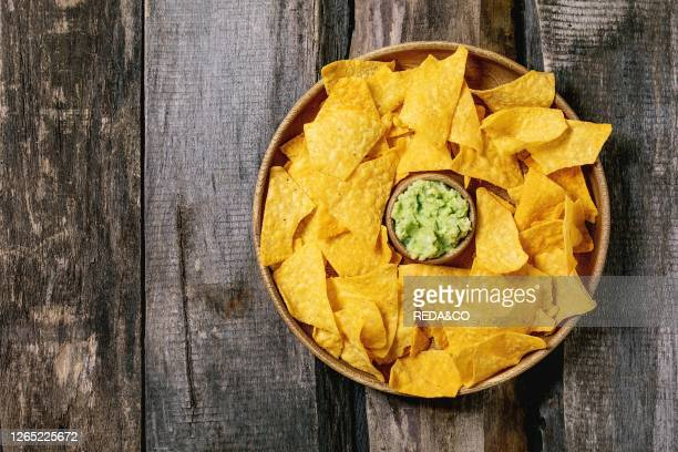 Tortilla nachos corn chips with avocado guacamole sauce served in wood plate over old wooden background Flat lay space