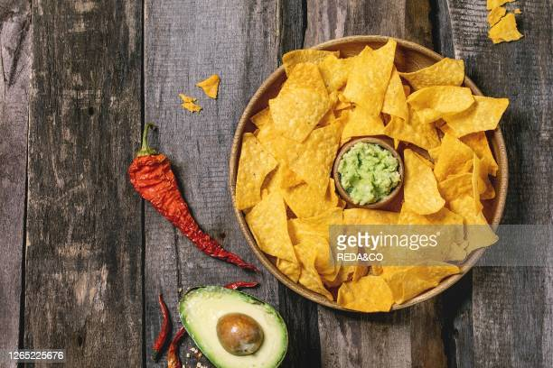 Tortilla nachos corn chips with avocado guacamole sauce served in wood plate with half of avocado and chilli peppers over old wooden background Flat...