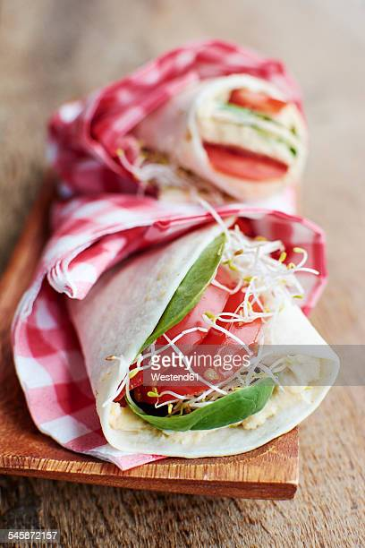 tortilla wraps with humus, spinach leaves, sprouts and tomato slices on wooden board - tortilla flatbread stock photos and pictures