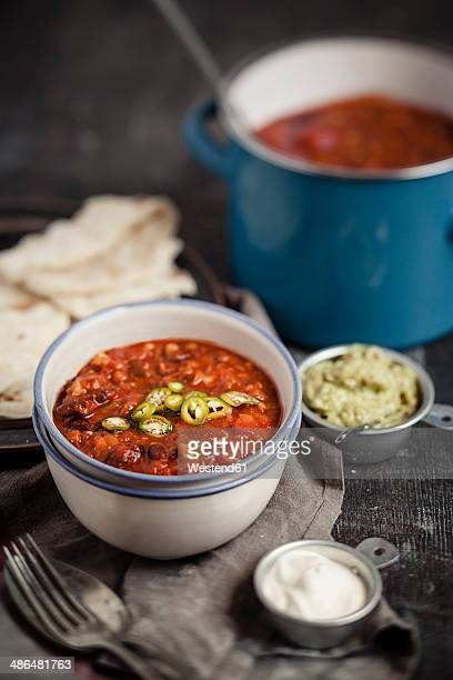 Tortillas and bowls of guacamole, sour cream, Chili con carne on wooden table