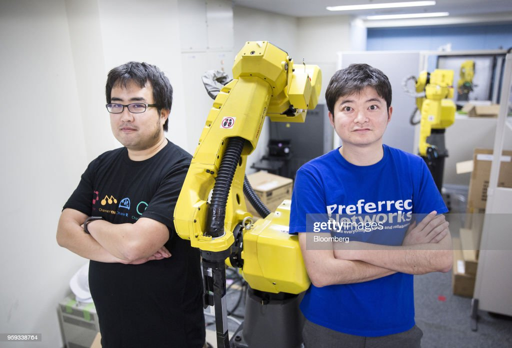 Toru Nishikawa, co-founder and chief executive officer of Preferred Networks Inc., right, and Daisuke Okanohara, co-founder and vice president, pose with a Fanuc Corp. robotic arm at their company's headquarters in Tokyo, Japan, on Friday, March 16, 2018. Preferred Networks has only one publicly available product, a whimsical application that uses artificial intelligence to automate the coloring of manga cartoons. Yet the four-year-old firm has become Japans most valuable startup, with a venture capital funding that priced it at more than $2 billion, according to people familiar with the matter. Photographer: Tomohiro Ohsumi/Bloomberg via Getty Images