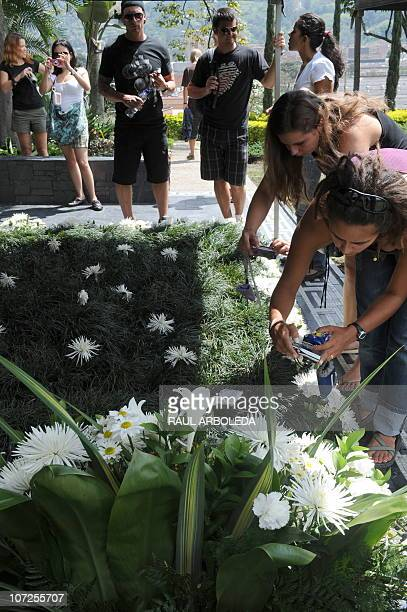 Toruists take pictures of the tombstone of Colombian drug lord Pablo Escobar at Montesacro cemetery on December 2 2010 in Medellin Antioquia...