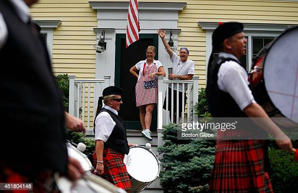 Tory Carlson center and Jon Cohen right watch from their balcony as the Fourth of July Parade goes by in Manchester By The Sea Mass July 2 2014