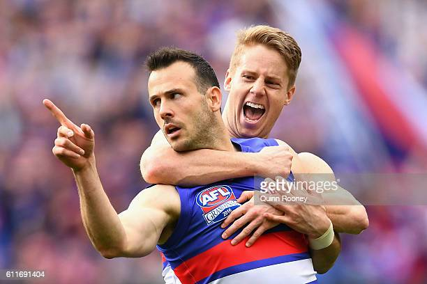 Tory Dickson of the Bulldogs is congratulated by Lachie Hunter after kicking a goal during the 2016 AFL Grand Final match between the Sydney Swans...