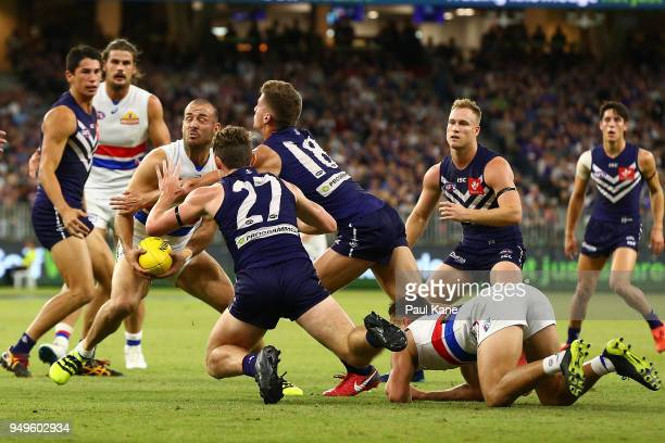 Tory Dickson of the Bulldogs looks to pass the ball before being tackled by Darcy Tucker of the Dockers during the round five AFL match between the...