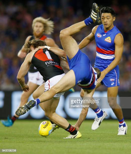 Tory Dickson of the Bulldogs tumbles over Andrew McGrath of the Bombers during the round three AFL match between the Western Bulldogs and the...