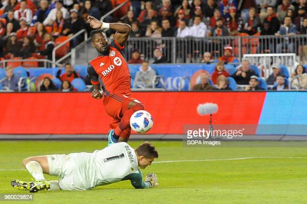 Tosaint Ricketts punches the ball through the goalkeeper during 2018 MLS Regular Season match between Toronto FC and Orlando City SC at BMO Field .