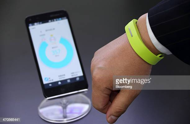 A Toshiba Corp employee demonstrates a Docomo Healthcare Inc Moveband a wearable technology device for easy recording and tracking of health data...