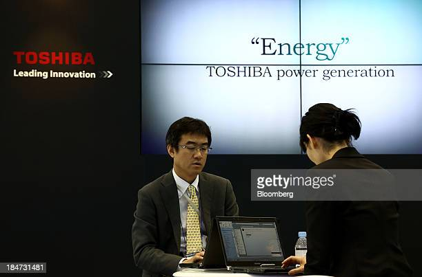 Toshiba Corp employees work at the company's booth at the the 22nd World Energy Congress in Daegu South Korea on Wednesday Oct 16 2013 The WEC a...