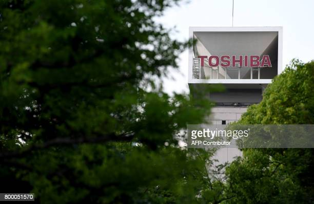 Toshiba corp logo is seen on the top of a building at the company's headquarters in Tokyo on June 23 2017 Toshiba delayed the release of its...