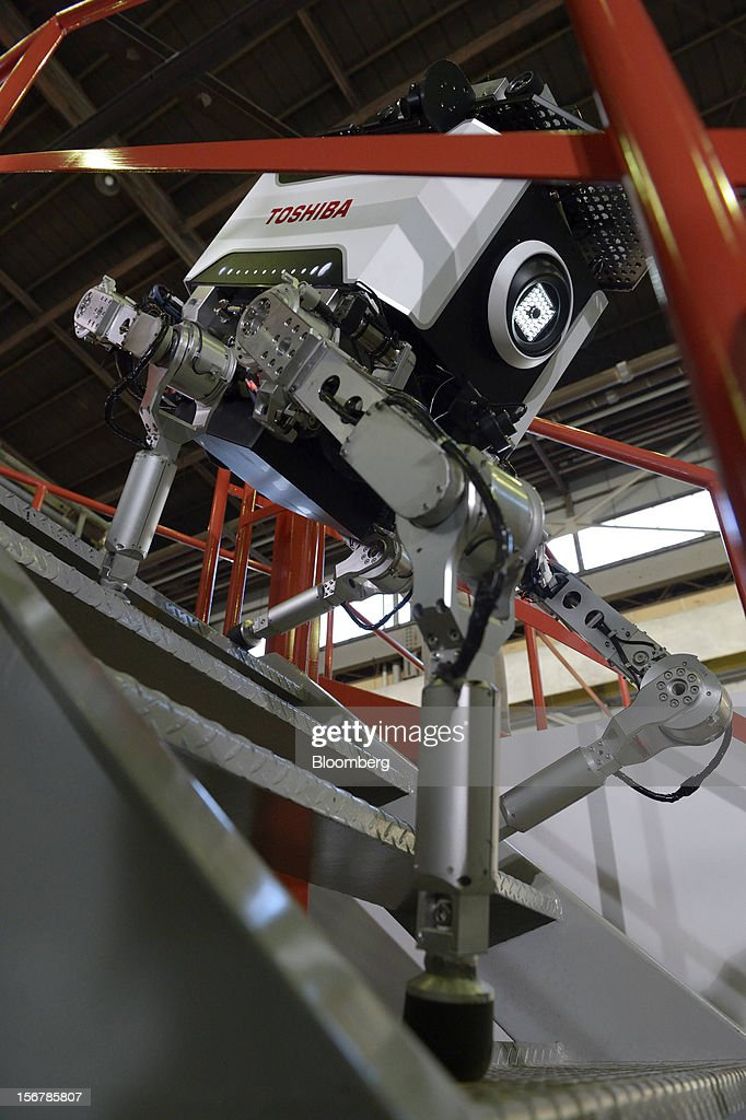 A Toshiba Corp. tetrapod robot walks down stairs at the company's Yokohama Complex in Yokohama City, Kanagawa Prefecture, Japan, on Wednesday, Nov. 21, 2012. Toshiba's new robot was developed to work in areas too dangerous for humans. Photographer: Akio Kon/Bloomberg via Getty Images