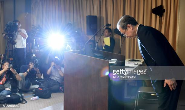 Toshiba's President Satoshi Tsunakawa bows during a press conference at the company's headquarters in Tokyo on August 10 2017 Toshiba on August 10...