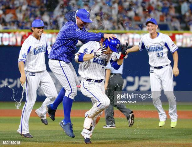 Toshihiko Kuramoto of the DeNA BayStars is mobbed by teammates after hitting a walkoff double in the ninth inning for a 32 win over the Chunichi...